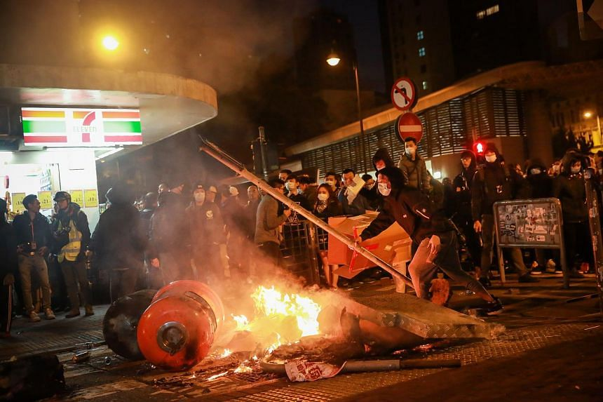 A rioter holds a lamp post as a fire burns in the Mongkok area of Hong Kong, on Feb 9, 2016.