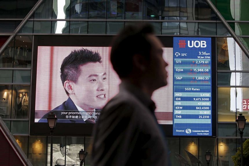 A man passes a board showing the Straits Times Index (STI) at the central business district in Singapore.