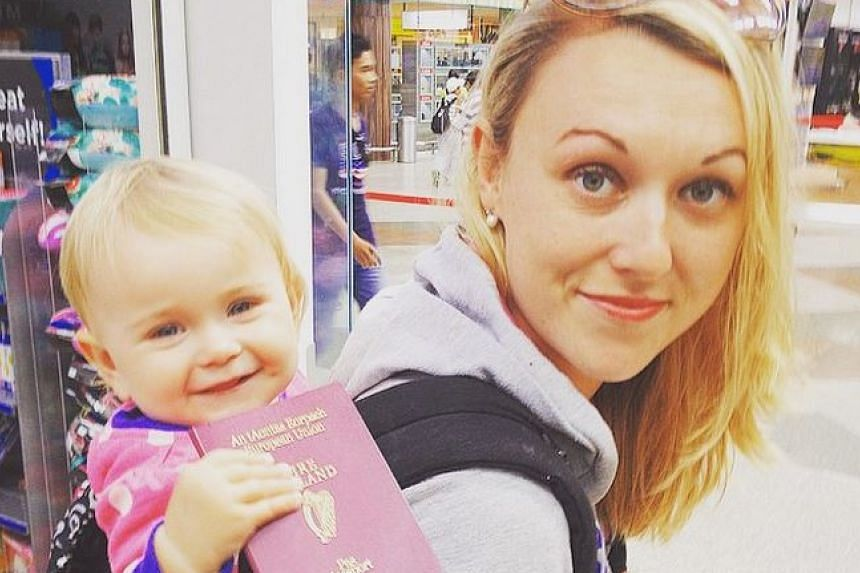 Ms Karen Edwards with her baby daughter Esme, seen here holding her passport, at the airport.