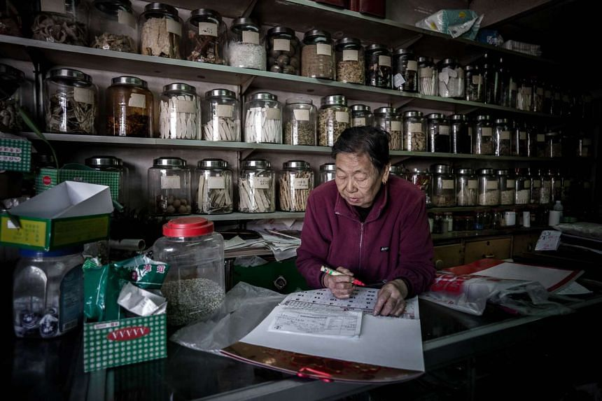 An elderly pharmacy owner at the counter of her shop outside the Nga Tsin Wai village in Hong Kong.