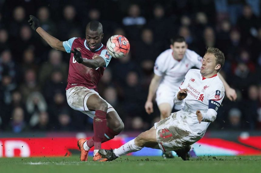 West Ham's Enner Valencia (left) is challenged by Liverpool's Lucas Leiva.