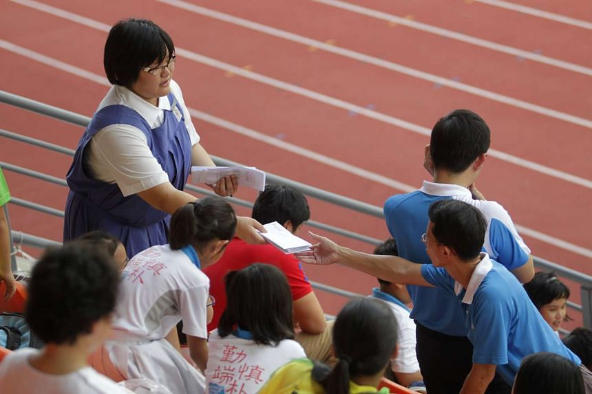 A secondary school student (left) handing out invitations at the national inter-primary school track and field championships to scout for student-athletes to join the school through the Direct School Admission (DSA) scheme.