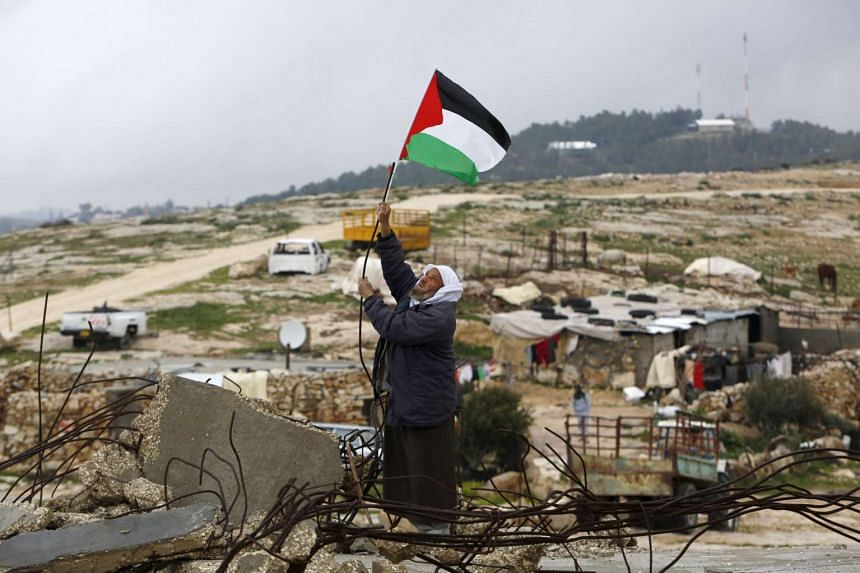 A man hangs a Palestinian flag atop the ruins of a mosque in the West Bank village of Mufagara, south of Hebron, on Jan 27, 2016.