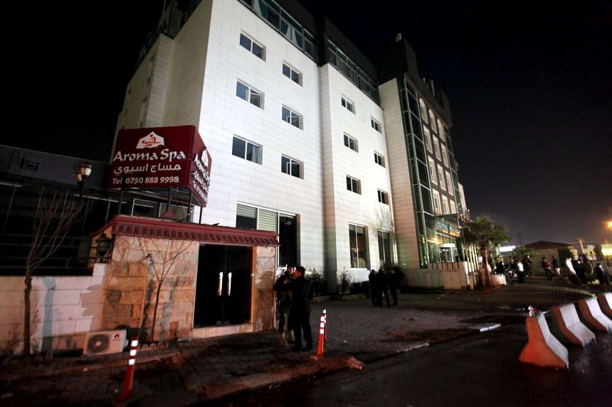 People gather at the Capitol Hotel, the site of a deadly fire, in Erbil, Iraq on Feb 5, 2016.