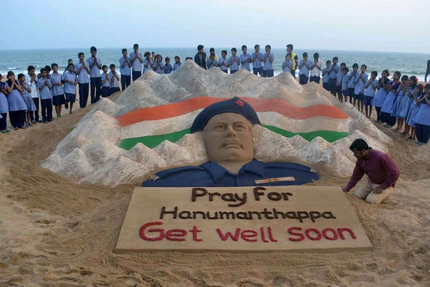 Indian students stand and pray near a sand sculpture created for Hanumanthappa Koppad.