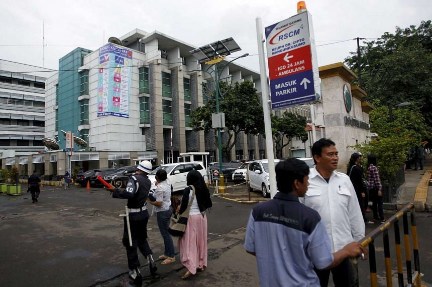 People walking past the gate of a government run hospital in Jakarta, Indonesia.