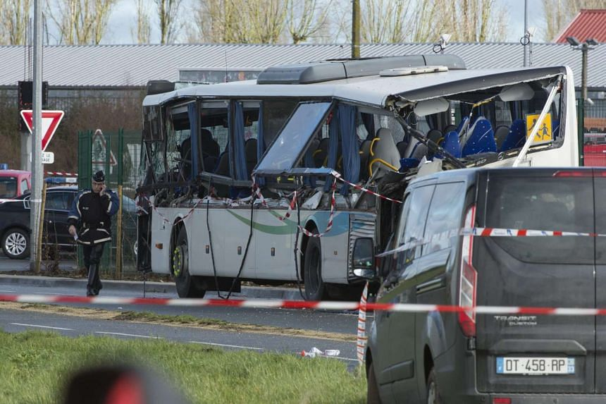 Police investigators work on a burned out bus at the accidents site in Rochefort, following the fatal bus crash.