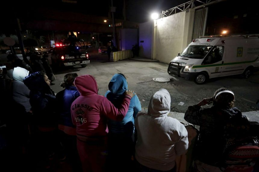 Family members of inmates stand outside Topo Chico Prison as an ambulance leaves the compound in Monterrey, Mexico.