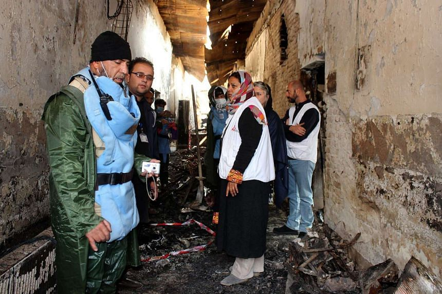 An Afghan worker (left) talks to staff members in a charred corridor of the Medecins Sans Frontieres (MSF) hospital in northern Kunduz.