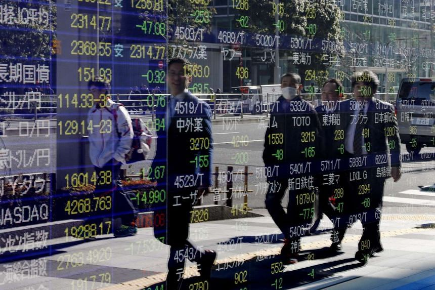 Businessmen walk past a monitor displaying Tokyo's stock index in in Tokyo, Japan,