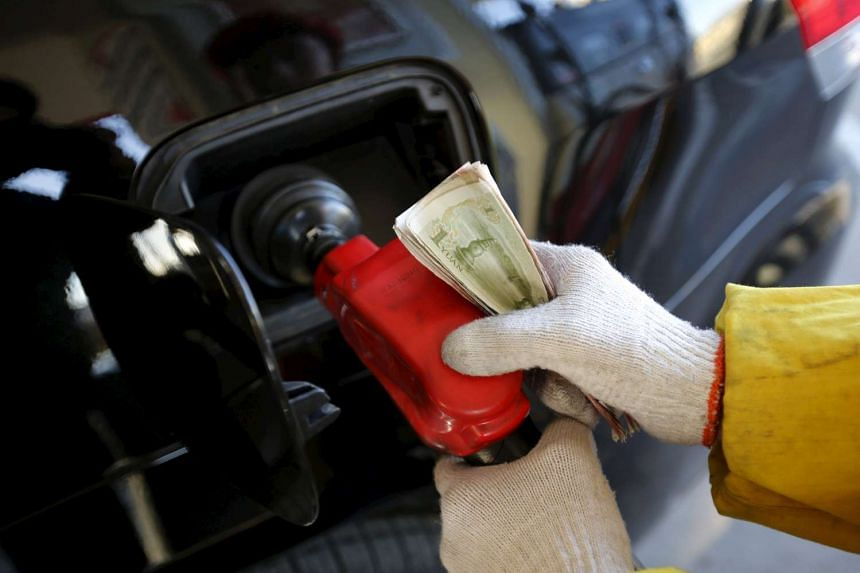 A gas station attendant feeds fuel into a customer's car in Beijing, on Jan 9, 2015.