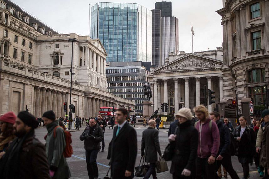 Pedestrians walk past the Bank of England in London.