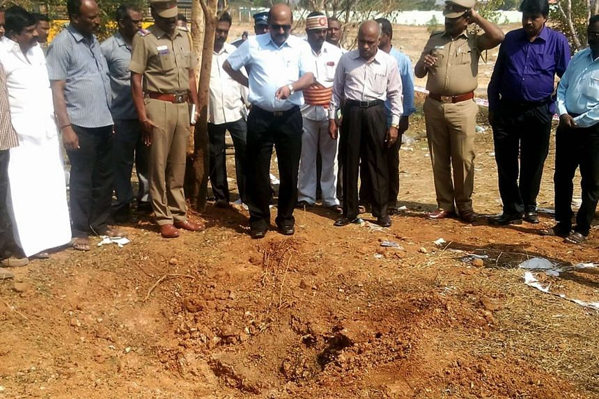 Indian authorities inspect the site of a suspected meteorite landing in southern Tamil Nadu state in an impact that killed a bus driver and injured three others on Feb 6.