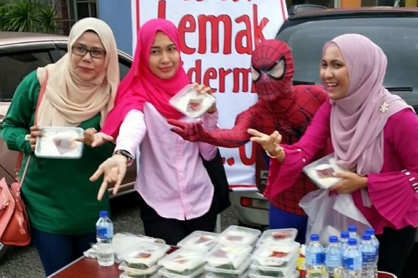 """""""Spider-Man"""" posing for a photo with his customers."""