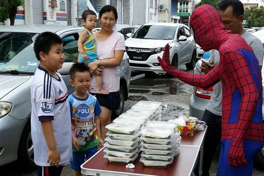"""Spider-Man"" interacting with visitors to his makeshift nasi lemak stall."