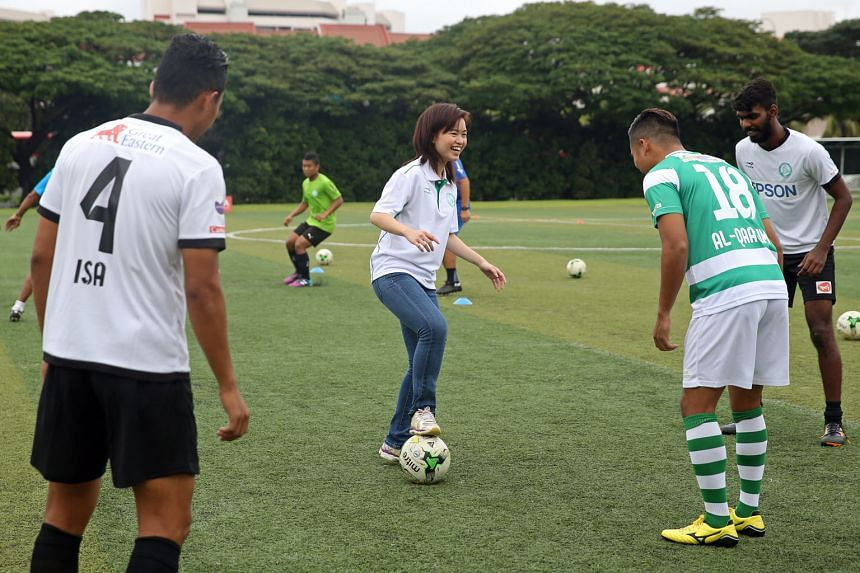 Geylang's Croatian forward Branko Cubrilo (above) signs an autograph for fan Bryan Lee during a meet-and-greet session yesterday. 0n the same pitch, Geylang's new adviser, MP Tin Pei Ling (left), takes on club defender Al-Qassimy Rahman during a kick-abou