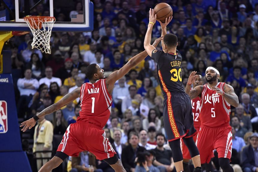 The Golden State Warriors' Stephen Curry shooting a three-pointer with the Houston Rockets' forward Trevor Ariza and centre Josh Smith defending. The point guard scored 35 points and the Warriors outlasted James Harden's game-high 37 to beat the Rockets 1