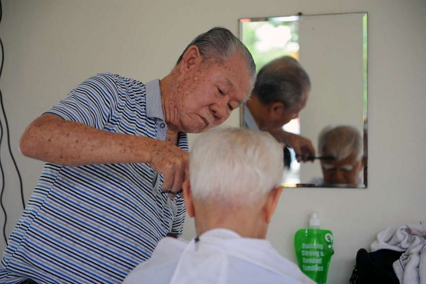 Mr Goh giving a free haircut to Mr Yaakop, one of his regular customers, to welcome Chinese New Year last week. Mr Goh has been volunteering his services at Paya Lebar Wellness Centre since retiring in 2006.