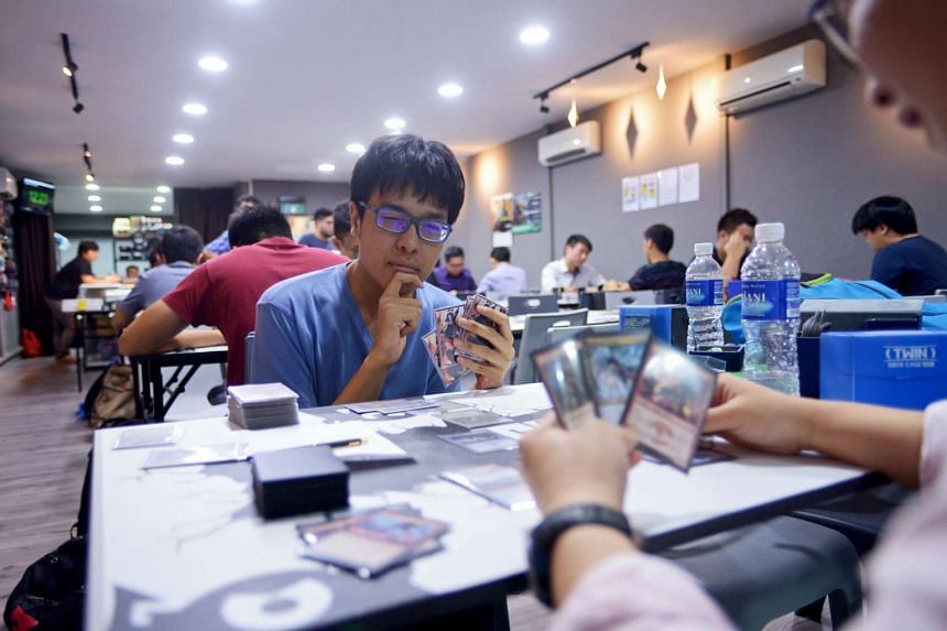 Players engrossed in a game of Magic: The Gathering at Grey Ogre Games. The shop in Club Street can seat up to 54 people and it is often packed with players on weekends and event nights. The shop's facilities are free, but players would typically buy