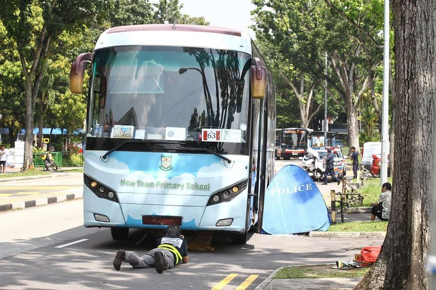 A forensics officer looking under the bus which hit Madam Ching Guan Eng on Nov 12, 2014.