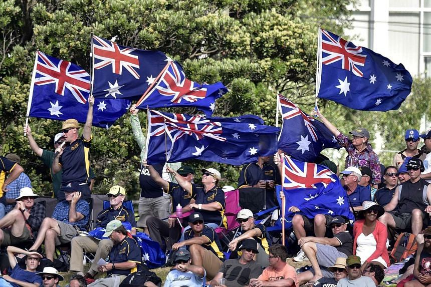 Australian fans wave flags during the first cricket Test match between New Zealand and Australia on Feb 12, 2016.