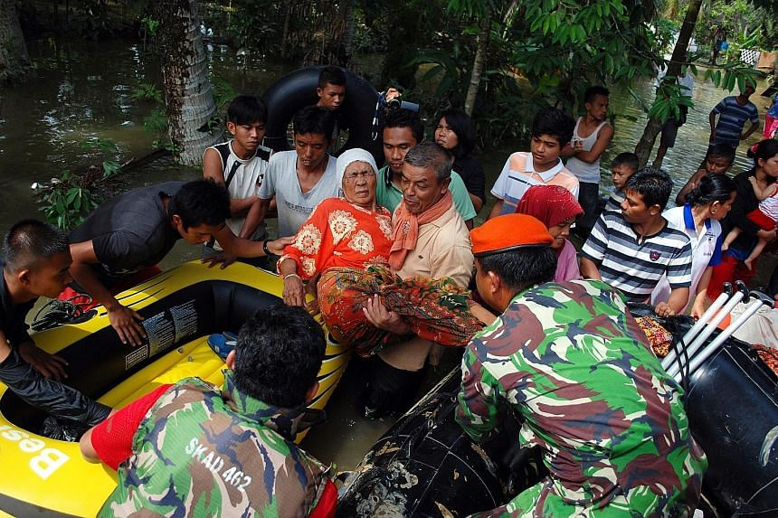 An elderly woman being evacuated using a rubber boat during flooding at Ranah village, in Kampar, Riau province, on Wednesday. Two people drowned in the raging floods in the worst-hit district of Kampar.