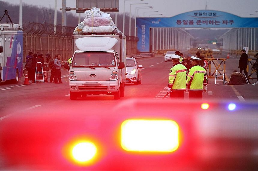 "A lorry leaving the Kaesong industrial zone in North Korea and passing a military checkpoint in Paju, South Korea, yesterday. Pyongyang called Seoul's decision to suspend operations at the park a ""declaration of war"", while South Korean firms slammed"