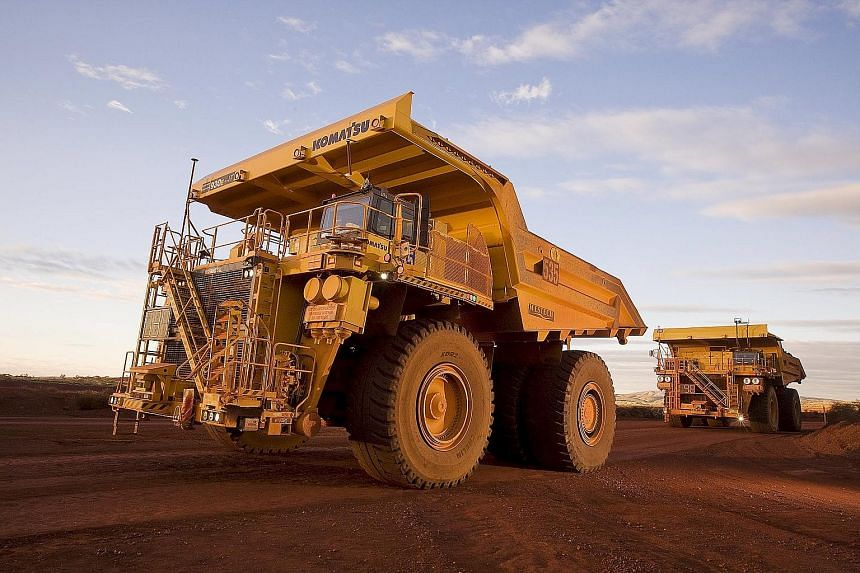 Giant haulage trucks at an iron ore mine in the Pilbara area of Western Australia in this photo provided by Rio Tinto. The company reported that underlying earnings fell to US$4.5 billion last year, from US$9.3 billion a year earlier.