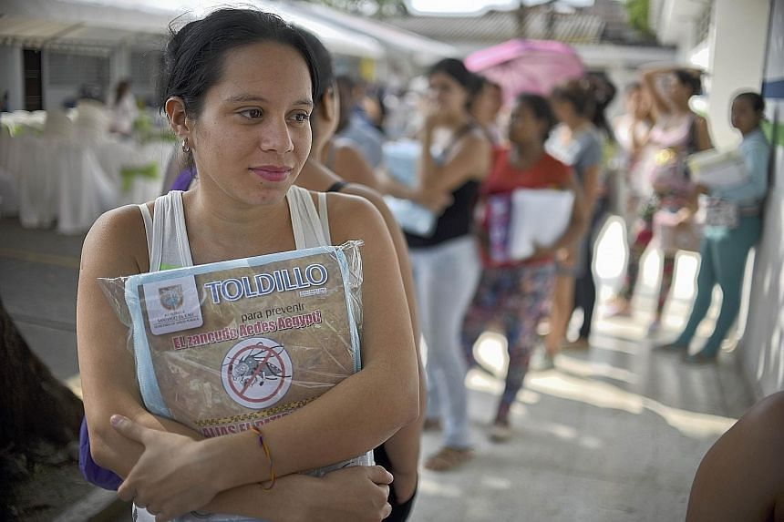A pregnant woman holding onto a mosquito net in Cali, Colombia, on Wednesday. The WHO advises women in areas with the virus to protect themselves, especially during pregnancy, by covering up against mosquitoes.