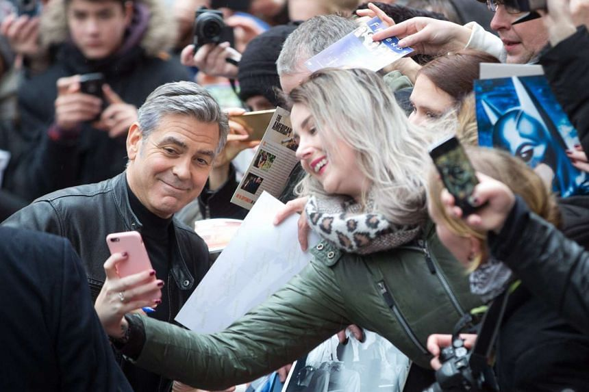 Clooney (left) poses with fans as he arrives at the photocall for Hail, Caesar!.