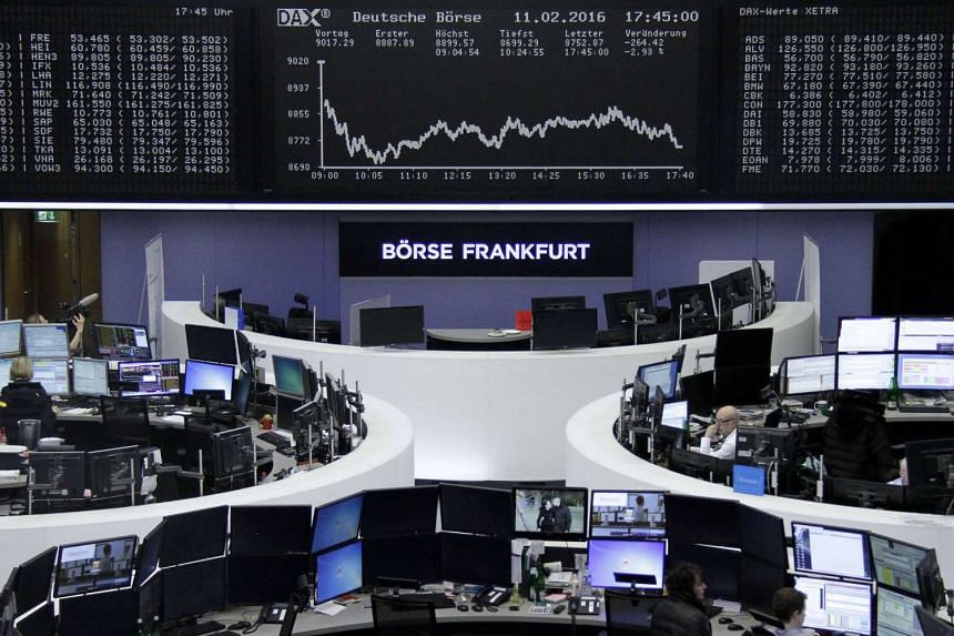 Traders work in front of the DAX board at the stock exchange in Frankfurt, Germany, on Feb 11, 2015.
