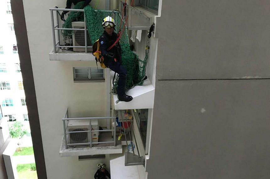 SCDF personnel preparing to place a protective net over the window of the unit below the man.