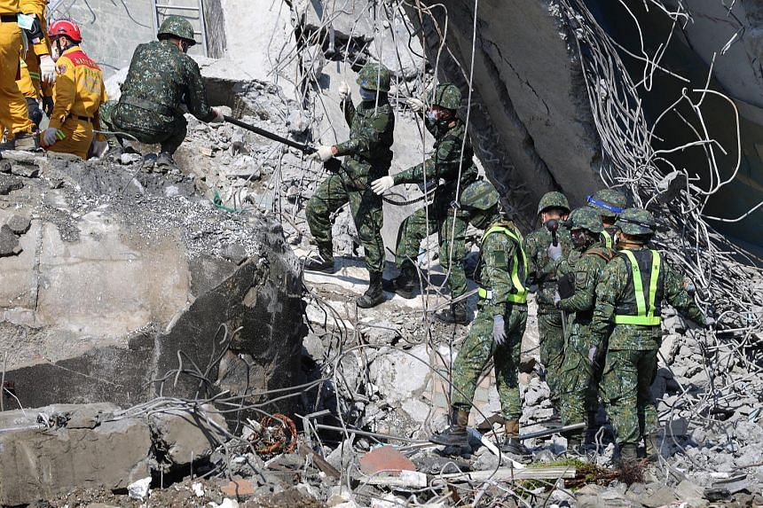 Soldiers and rescuers search for survivors in a collapsed building in Tainan City, Taiwan, on Feb 10, 2016, in this handout photo from the Taiwanese Military News Agency.
