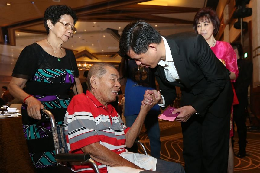 NTUC secretary-general Mr Chan presenting a red packet to Mr Leo, a former marine chief engineer and SMOU member, who is accompanied by his wife, Madam Dan (left), during the SMOU 65th anniversary Chinese New Year luncheon and hongbao presentation yesterd