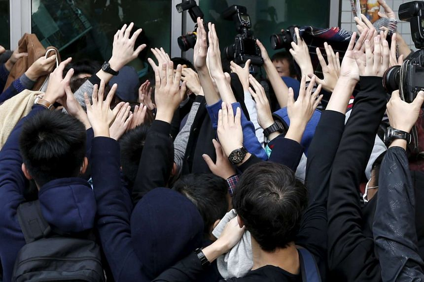 Supporters raising their hands (above) to try to shield a protester from the media as he left a court in Hong Kong yesterday.