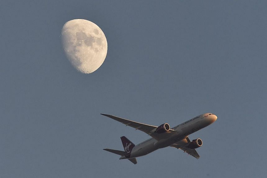 A Virgin Atlantic plane with the moon in the background.