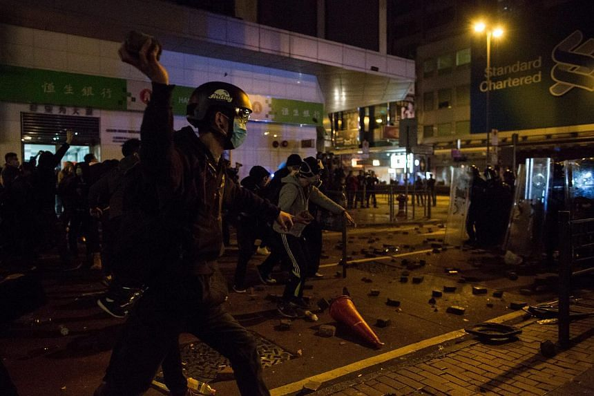 A protester (left) prepares to throw a brick at police during riots in Mongkok district in Hong Kong, China, on Feb 9, 2016.