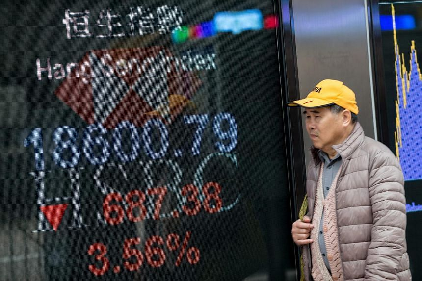 A man walks past an electronic billboard displaying the Hang Seng Index numbers in Hong Kong, China, on Feb 11, 2016.