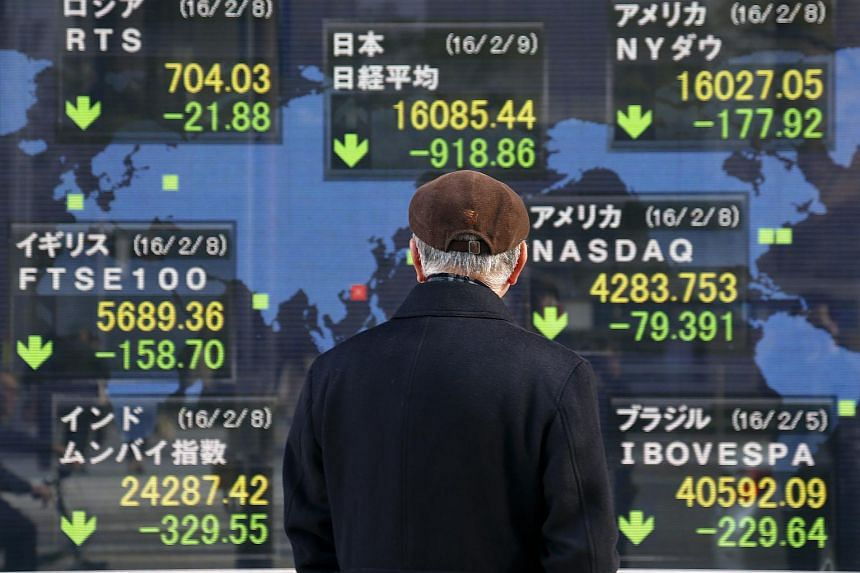 A pedestrian looks at closing information of the Tokyo's Nikkei Stock Average and other global stock markets in Tokyo, Japan.