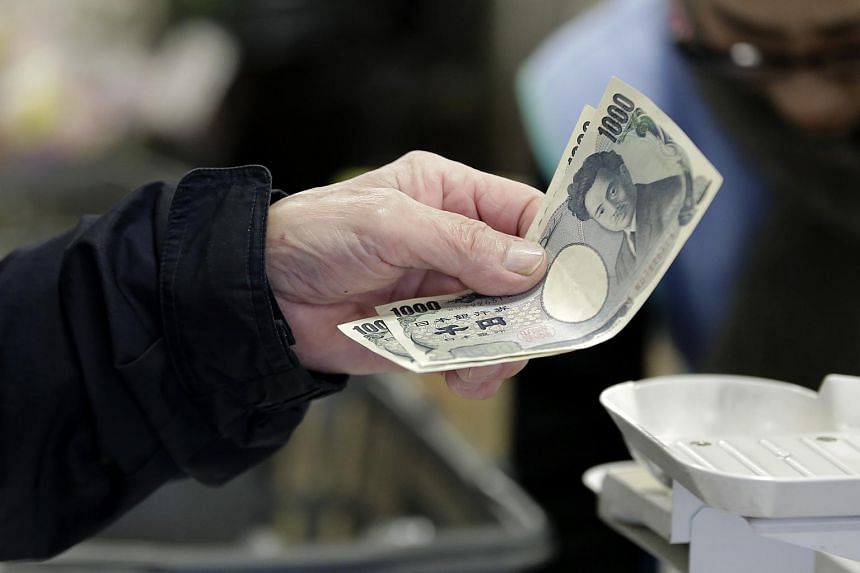 A customer hands over 1,000 yen banknotes while making a purchase in Tokyo, Japan.