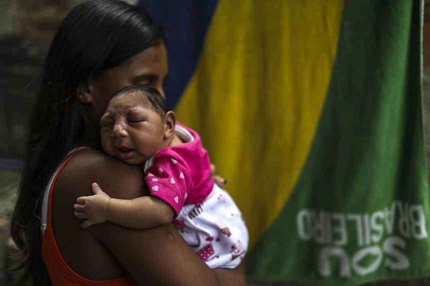 A mother in Brazil holds her daughter, born with microcephaly after being exposed to the zika virus during her mother's pregnancy.