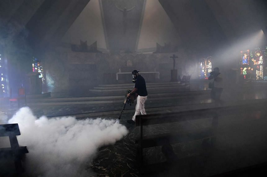 A health worker fumigating inside a church in Caracas on Feb 5.