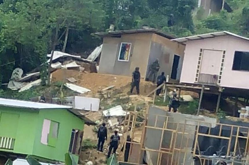 Security personnel checking the houses at the settlement in Saturday's dawn operation.