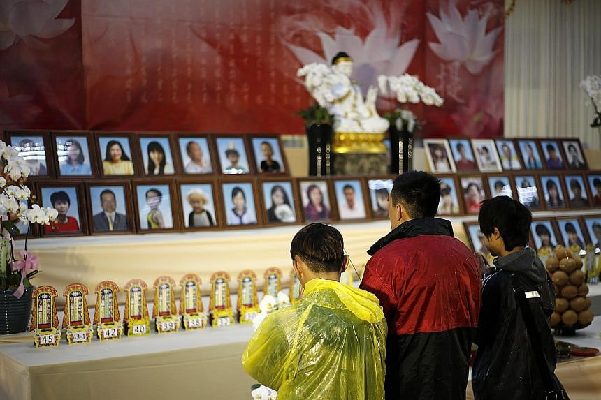 Relatives attending a memorial service for quake victims in Tainan yesterday. The 6.4-magnitude quake has left at least 96 people dead, and 94 of them were residents of a building that collapsed.