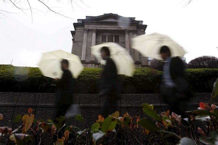 Pedestrians with umbrellas walking in front of the Bank of Japan headquarters in Tokyo on Jan 29.