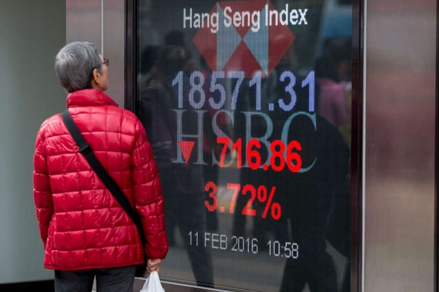 A woman looking at an electronic billboard displaying the Hang Seng Index numbers in Hong Kong, on Feb 11, 2016.