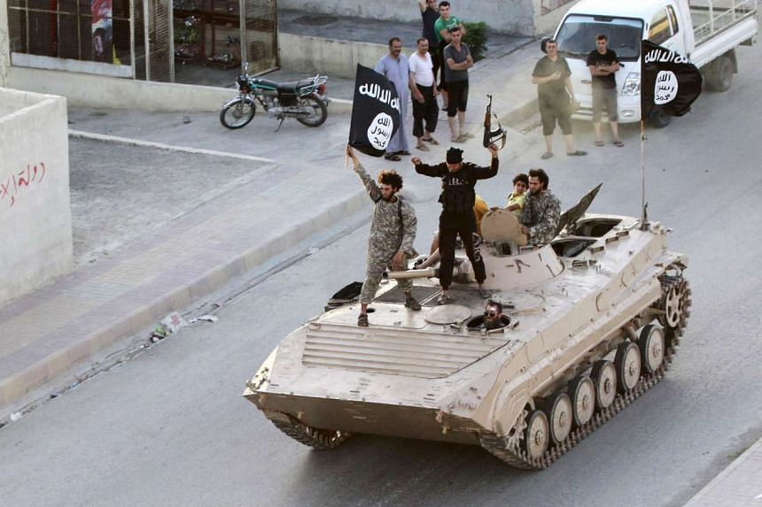 Militant Islamist fighters in a military parade along the streets of northern Raqqa province in a 2014 file photo.