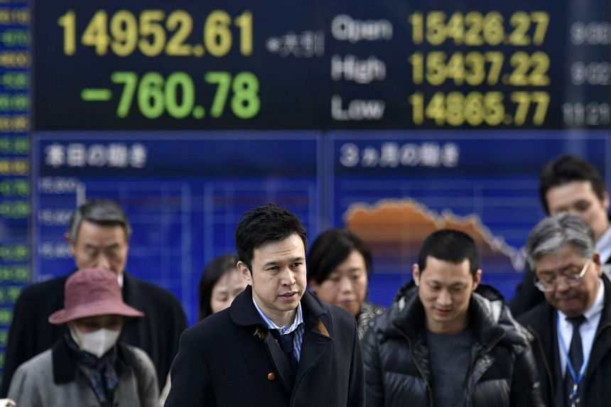 Pedestrians standing in front of a stock market indicator board in Tokyo on Feb 12.