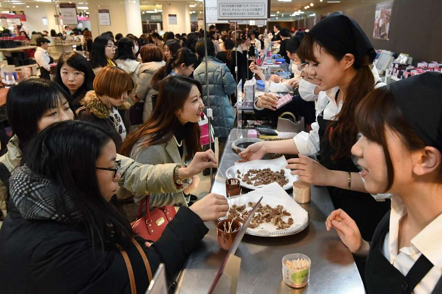 Vendors recommending chocolates to customers at the Printemps department store in Tokyo on Feb 9, 2016, before Valentine's Day on Feb 14.