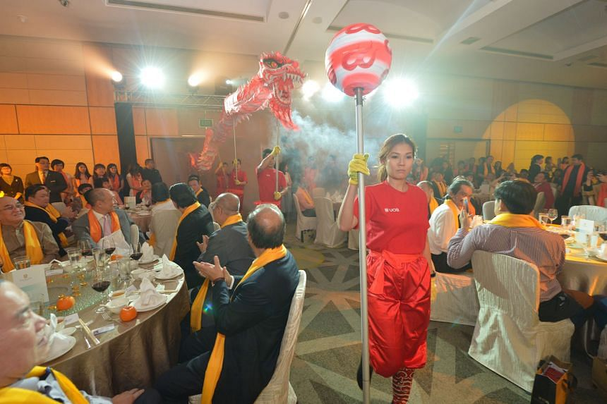 Ms Joey Kirk, vice-president of enterprise banking at United Overseas Bank (UOB) Group, led senior staff in a dragon dance for charity as UOB Group deputy chairman and chief executive officer Wee Ee Cheong (seated second from left, with pink tie) looked o